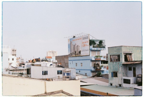 Billboard on the side of a 'tube' house. The view from Kenh Te Bridge, District 4, HCMC
